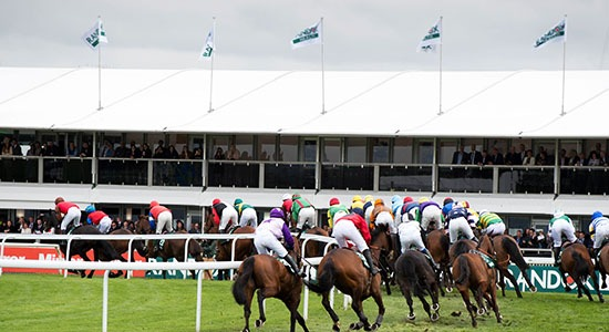 Horses running past the Silks Restaurant at Aintree Racecourse on Grand Opening Day